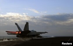 A U.S. Navy handout photo dated February 13, 2012 shows a F/A-18E Super Hornet fighter jet launching from the flight deck of the aircraft carrier USS Abraham Lincoln, part of the Bahrain-based U.S. 5th Fleet.