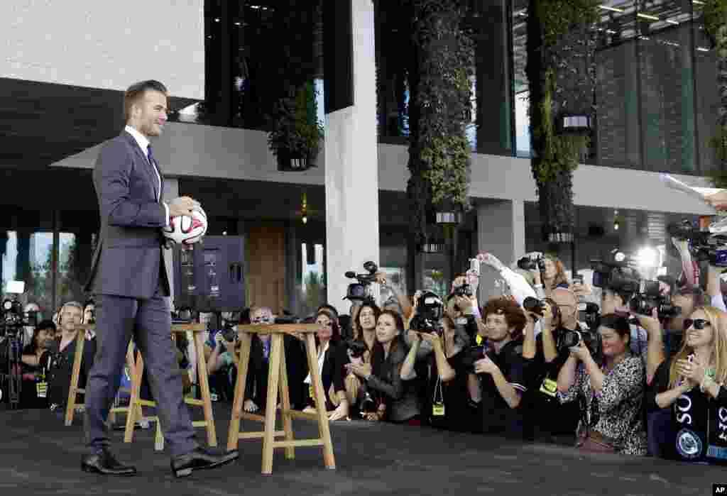 Cựu cầu thủ bóng đá ngôi sao David Beckham cầm một quà bóng trong một cuộc họp báo tại Miami ông loan báo sẽ mua một đội bóng tại Miami, Florida.