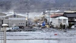 A tsunami wave washes away houses in Kesennuma, Miyagi prefecture, on March 11