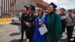"""ຊາວເມັກຊິໂກ ທີ່ເອີ້ນວ່າ ພວກ """"ນັກຝັນ"""" ຫລື """"Dreamers"""" ໃສ່ຊຸດຮັບປະລິນຍາ ຍ່າງກອດແຂນກັນ ໄປປະທ້ວງ ເພື່ອສະແດງເຖິງຄວາມໄຝ່ຝັນຂອງເຂົາເຈົ້າ ທີ່ຢາກຮຽນໃຫ້ຈົບ ຢູ່ໃນສະຫະລັດ ເພື່ອຕໍ່ຕ້ານນະໂຍບາຍກວດຄົນເຂົ້າເມືອງຂອງ ສະຫະລັດ ຢູ່ດ່ານຊາຍແດນຕິດກັບ Mexico ໃນວັນທີ 22 ກໍລະກົດ 2013."""