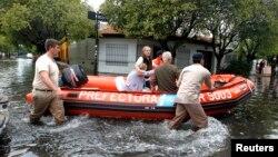 Nhân viên cứu hộ Argentina sơ tán 2 phụ nữ sau khi mưa làm ngập lụt phần lớn thành phố La Plata, ngày 3/4/2013.
