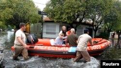 Penjaga pantai Argentina mengevakuasi dua perempuan dari wilayah mereka yang terendam banjir di LaPlata (3/4).