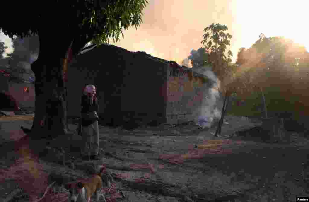 A woman looks at burning houses in Bossangoa, north of Bangui, Jan. 3, 2014.