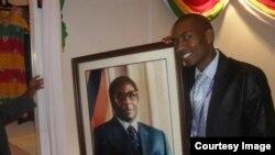 Chief Economist Kipson Gundani holding a portrait of President Robert Mugabe.