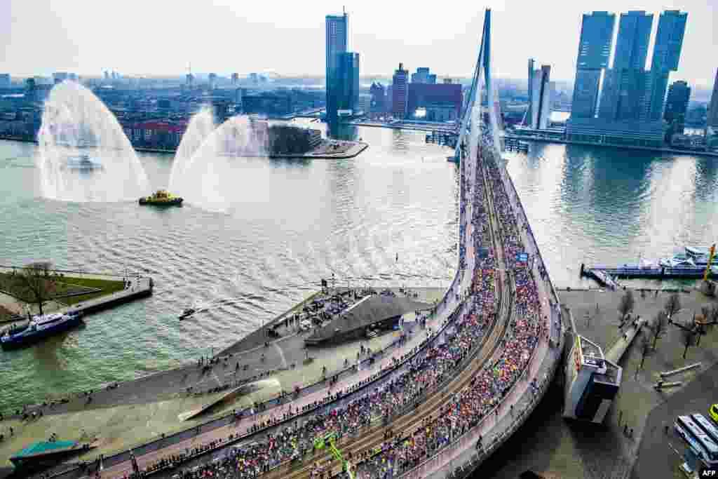មនុស្សម្នារត់កាត់ស្ពាន Erasmus ក្នុងការរត់ប្រណាំងម៉ារ៉ាតុន Rotterdam Marathon លើកទី៣៨ នៅក្នុងក្រុង Rotterdam ប្រទេសហូឡង់។