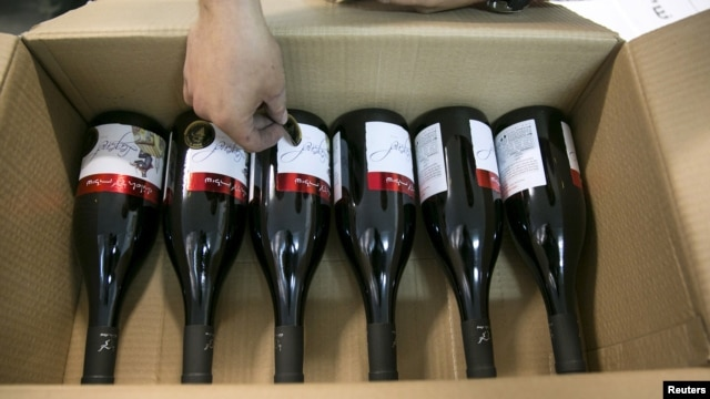 FILE - A worker places stickers on wine bottles while packaging them for export at Shiloh Wineries, north of the West Bank city of Ramallah, Nov. 8, 2015.