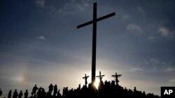 Flanqueados por La Cruz del El Morro, penitentes recrean la crucifixión de Jesucristo, el viernes, 30 de marzo, de 2018, durante la celebración del Vienes Santo.