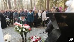 A girl scout lays a wreath at the central monument of a cemetery near the village of Jagiella, in southern Poland, Thursday, March 17, 2016 during ceremonies remembering the Ulma family and eight Jews they were sheltering during Holocaust, all of whom wer