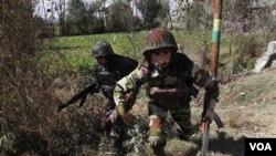 Tentara India mengambil posisi saat mengepung rumah militan di luar kota Srinagar, Kamis pagi 21 Oktober 2010.