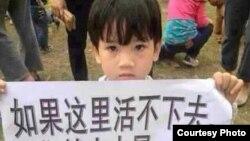 一名参加茂名抗议的儿童举着标语牌:如果这里活不下去,我们就去火星……