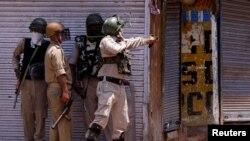 Seorang polisi India menggunakan ketapel untuk melemparkan batu ke arah para pemrotes saat terjadi bentrokan pada peringatan pembunuhan pasukan India Burhan Wani, komandan kelompok militan Hizbul Mujahidin, di pusat kota Srinagar, 8 Juli 2017.
