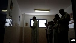 In this photo taken on June 23, 2017, inmates pray with the Imam Mimoun El Hachmi, left, inside the Terni penitentiary.