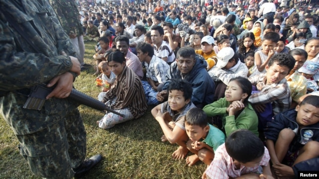 A Thai soldier stands guard as refugees from Burma sit at the Thai-Burma border town of Mae Sot, waiting to go to refugee camps in Thailand, November 9, 2010.
