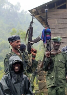 M23 rebel fighters stand in the rain at Rumangabo after government troops abandoned the town, north of the eastern Congolese city of Goma, July 28, 2012.