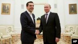 PM Yunani Alexis Tsipras (kiri) berjabat tangan dengan Presiden Rusia Vladimir Putin dalam kunjungannya ke Moskow, Rabu (8/4).