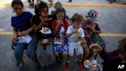 Anak-anak migran menyantap makanan yang disediakan oleh badan amal di Texas, di jembatan internasional Puerta Mexico, Matamoros, negara bagian Tamaulipas, Meksiko, 27 Juni 2019.