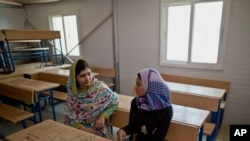 FILE - Nobel Peace Prize laureate Malala Yousafzai, 18, left, and Mezon al-Melihan, a 17-year-old refugee from the southern Syrian town of Deraa, talk while visiting a class at Azraq refugee camp, Jordan, July 13, 2015.