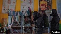 Seorang petugas medis meyemprotkan disinfektan di sebuah sekolah di Palu, Sulawesi Tengah, untuk mencegah penyebaran virus corona baru (COVID-19), 20 Maret 2020. (Foto: Antara via Reuters)