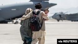 A family walks towards a US Air Force Boeing C-17 Globemaster III during an evacuation at Hamid Karzai International Airport, Afghanistan, Aug. 22, 2021. (US Marine Corps photo)