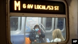 In this March 19, 2020 photo, a commuter wears a face mask while riding the subway in New York.