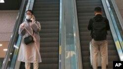 25일 한국 인천 국제공항에서 보호장비를 착용한 여성이 에스컬레이터를 타고 내려오고 있다.