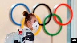 Un atleta alemana, con mascarilla, pasa junto a la exhibición de anillos olímpicos a su llegada al aeropuerto de Haneda en Tokio, el 1 de julio de 2021.