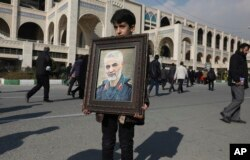 "A boy carries a portrait of Iranian Revolutionary Guard Gen. Qassem Soleimani, who was killed in the U.S. airstrike in Iraq, prior to the Friday prayers in Tehran, Iran, Friday Jan. 3, 2020. Iran has vowed ""harsh retaliation"" for the U.S. airstrike…"