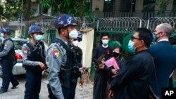 Mjanmarska policija razgovara sa ljudima koji se okupljaju ispred suda Kamayut u Jangonu, 12. marta 2021.