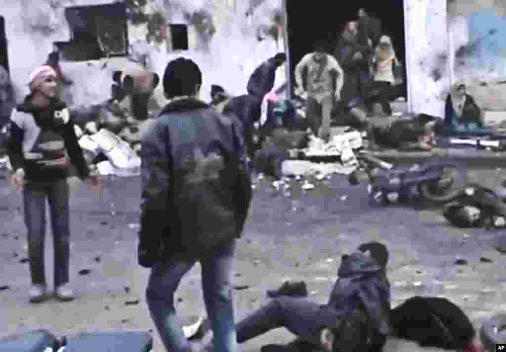 在政府军12月23日对叙利亚哈马郊外进行空袭后,叙利亚人帮助抬走在空袭中被炸死的人的遗体