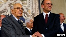Italian Prime Minister-designate and deputy leader of the centre-left Democratic Party (PD) Enrico Letta (R) shakes hands with President Giorgio Napolitano at the Quirinale Palace in Rome, April 27, 2013.