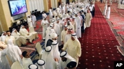Kuwaitis queue at the Grand Mosque to pay their respects and condolences to the families of victims of a terrorist attack claimed by the Islamic State group on the Shiite Imam Sadiq Mosque in Kuwait City during Friday prayers, June 28, 2015.