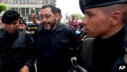 El ex ministro de Interior de Guatemala, Mauricio López Bonilla, es escoltado por la policía cuando llega a un tribunal de la ciudad de Guatemala el sábado 11 de junio de 2016.