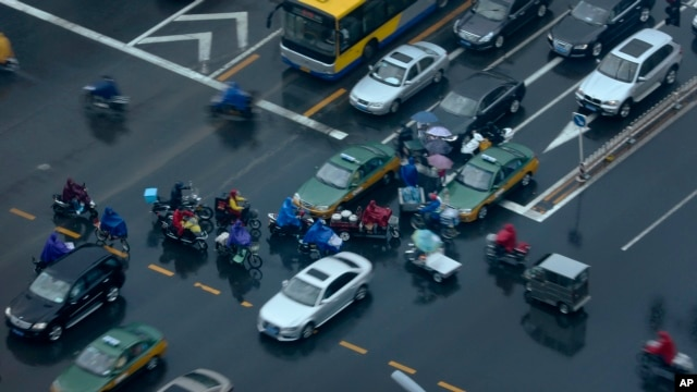 FILE - People on electric bikes cross a busy traffic intersection on a rainy day on Chang'an Avenue in Beijing, China.