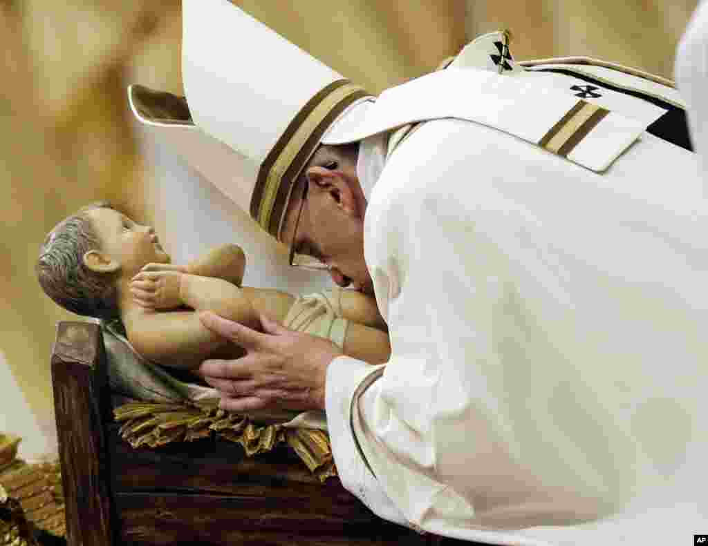 Pope Francis kisses a statue of Baby Jesus as he celebrates the Christmas Eve Mass in St. Peter's Basilica at the Vatican, Dec. 24, 2014.