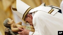 Pope Francis kisses a statue of Baby Jesus as he celebrates the Christmas Eve Mass in St. Peter's Basilica at the Vatican, Wednesday, Dec. 24, 2014.