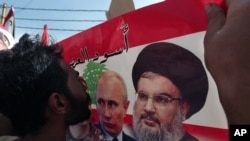 FILE - A Syrian who lives in Lebanon kisses a poster with photos of Russian President Vladimir Putin (C) and Hezbollah leader Sheikh Hassan Nasrallah, during a rally to thank Moscow for its intervention in Syria, in front of the Russian embassy in Lebanon, Oct. 18, 2015.