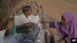 肯尼亚一个难民营的儿童在分到世界粮食机构提供的食品后乘驴车离去(资料照片)
