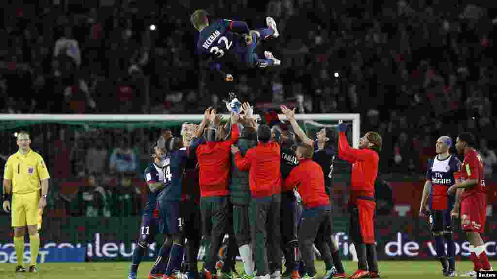 Paris Saint-Germain players throw David Beckham in the air at the end of their team's French Ligue 1 soccer match against Brest in Paris May 18, 2013.
