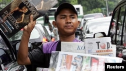 Seorang penjaja koran menawarkan koran dan majalah kepada para pengendara motor di sebuah jalan di Jakarta, 7 Juni 2006. (Foto: Reuters)