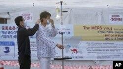 Seorang pasien memakai masker untuk melindungi diri dari penyakit MERS, di Seoul National University Hospital, Korea Selatan (1/6). (AP/Ahn Young-joon)