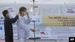 Một bệnh nhân đeo khẩu trang để tránh bị lây nhiễm bệnh MERS, hội chứng hô hấp Trung Đông, tại Bệnh viện Đại học Quốc gia Seoul, ngày 1/6/2015. Vi rút MERS trong giai đoạn đầu gây ra những triệu chứng giống bệnh cúm, như sốt và ho, nhưng sau đó nó có thể dẫn tới viêm phổi và suy thận. Chưa có thuốc điều trị hay vắc xin cho bệnh MERS.