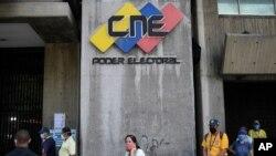 Personas con tapabocas esperan en una fila cerca de la entrada a la sede del Consejo Electoral en Caracas, Venezuela.