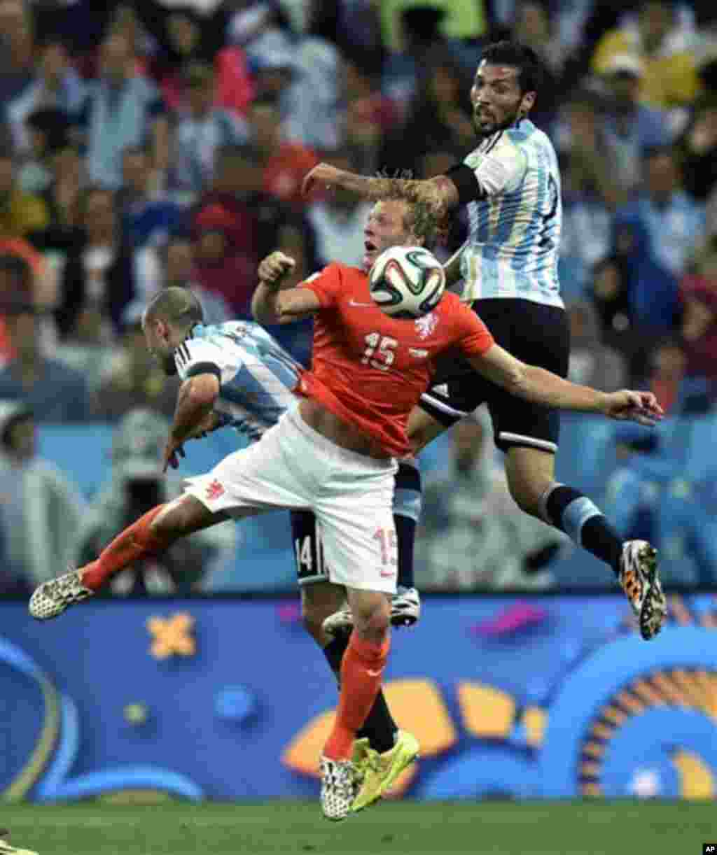 Netherlands' Dirk Kuyt is challenged by Argentina's Javier Mascherano, left, and Ezequiel Garay during the World Cup semifinal soccer match between the Netherlands and Argentina at the Itaquerao Stadium in Sao Paulo Brazil, Wednesday, July 9, 2014. (AP Ph
