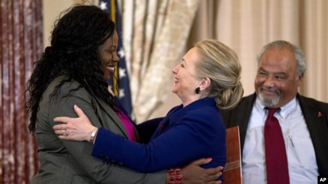 Secretary of State Hillary Rodham Clinton greets Florence Ngobeni-Allen, ambassador for the Elizabeth Glaser Pediatric AIDS Foundation during a ceremony in recognition of World AIDS Day, at the State Department in Washington, D.C., November 29, 2012.