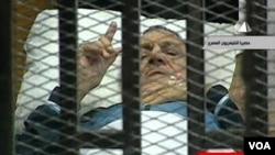 Gambar dari televisi Mesir menunjukkan mantan Presiden Hosni Mubarak memberi gerak isyarat di ruang persidangan di akademi polisi di Kairo (15/8).