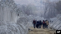 FILE - Refugees and migrants, who entered Macedonia from Greece illegally, walk between the two lines of the protective fence along the border line, near southern Macedonia's town of Gevgelija, Feb. 29, 2016.