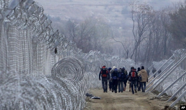 FILE - Refugees and migrants, who entered Macedonia from Greece illegally, walk between the two lines of the protective fence along the border line, near southern Macedonia's town of Gevgelija, Monday, Feb. 29, 2016.