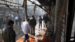 Người dân Syria bước qua những vũng máu và đống đổ nát ở khu vực Damascus sau vụ bố ráp của binh sĩ Syria khiến một số chiến binh nổi dậy và thường dân thiệt mạng, ngày 5/4/2012.