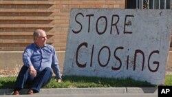 """მამაკაცი თავისი მაღაზიის წინ, წარწერით: """"მაღაზია იკეტება"""""""