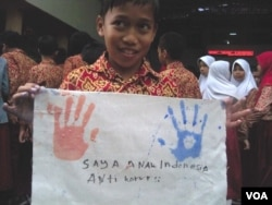 Seorang siswa SD di Bandung memperlihatkan kain integritas hasil karyanya. (VOA/R. Teja Wulan)